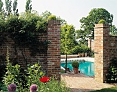 Opening in brick wall with view of pool and trees