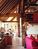 Various seating areas in barn converted into apartment with exposed roof timbers