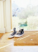 Baseball boots on doormat