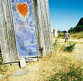 Weathered wooden shed with heart motif