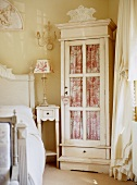 Glass-fronted cabinet with curtain in traditional, romantic bedroom