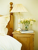 Bedside table with lamp, book and flowers
