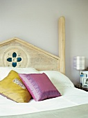Yellow and violet scatter cushions on romantic wooden bed