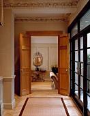 Stuckdecke im Vorraum einer Villa mit offen stehenden Flügeltüren und Blick in Wohnraum