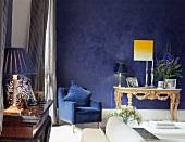 Blauer Sessel neben Rokoko Tischchen an blau getönter Wand