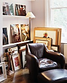 Comfortable leather armchair with matching footstool in front of shelves with collection of pictures