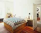 Double bed with ethnic bedspread next to open door in bedroom