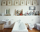 Bathroom fittings against white-tiled wall and framed pictures on shelf