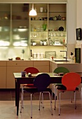 Colourful Bauhaus chairs in dining area in front of half open kitchen cupboard