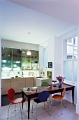 Colourful Bauhaus chairs in dining area in open-plan kitchen
