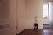 Guitar leaning on wall on floorboards in foyer