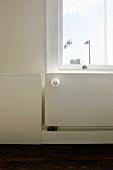 Radiator below window integrated into half-height wood panelling