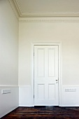 White-painted, panelled door and old floorboards in grand anteroom