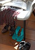 Various women's shoes under chair on dark floorboards