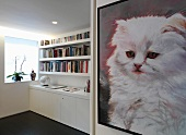 Picture with cat motif on wall of anteroom and bookcase above white sideboard