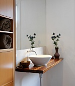 Minimalist washstand with white ceramic basin on wooden counter in corner of bathroom