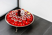 Tray with red tea light holders on grey tiled floor