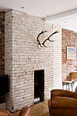 Deer antlers on exposed brick wall above fireplace