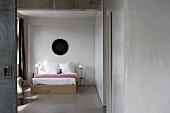 View of simple double bed in bedroom with screed floor through open door