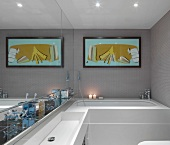 Washstand against mirrored wall and modern picture above bathtub in designer bathroom