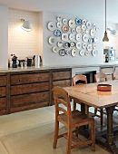 Rustic dining table in front of kitchen unit and collection of plates on wall