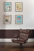 Old swivel chair with brown leather upholstery against wall with framed pictures