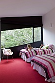 Girl reading comfortably on one of two twin beds with striped covers in designer bedroom