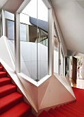 Staircase with red carpet in contemporary apartment building with futuristic ambiance