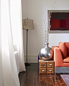 Silver-coloured vase on low, wooden cabinet and standard lamp in corner of living room