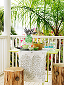 Delicate table and stools made of sections of tree trunk on veranda with white-painted balustrade and view of tropical garden