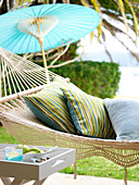 Cushions in hammock and Chinese paper parasol on terrace