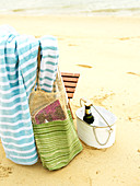 Beach bag and towel hung over chair and drink in metal bucket on sandy ground