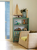 Rattan armchair in front of painted shelves in corner of living room