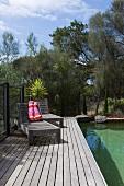 Verwitterte Holzliegen auf Dielen am Pool in mediterranem Garten