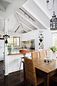 Wooden table and rattan chairs in dining area in front of open-plan kitchen in simple house with white wooden ceiling