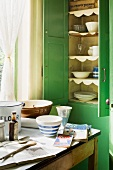 Green-painted wooden cupboard with open doors