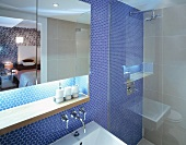 Mirrored cabinet with indirect lighting and shower against wall with blue mosaic tiles