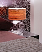 Bedside lamp with transparent, acrylic glass base against patterned wallpaper