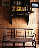 Wooden bench below wall-mounted Oriental shelves on rustic wooden wall