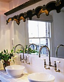 Wash basins on tiled washstand with vintage-style, wall-mounted tap fittings below mirror