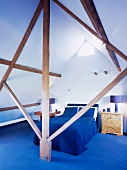 View through wooden structure of bed with blue bedspread and blue carpet in attic room
