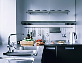 Work surface with stainless steel sink and wall light above hanging kitchen utensils