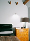 Biedermeier-style bedside cabinet with modern bedside lamp next to bed