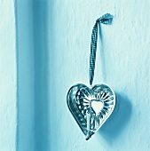 Heart-shaped baking tin used as candle holder hanging on wall