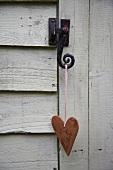 Ein Herz hängt am Schloss einer Holztür