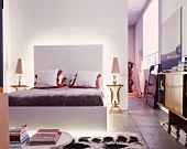 Loft apartment with open-plan sleeping area and modern bed with indirect lighting