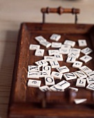 Game tiles with letters on wooden tray