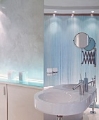 Washstand and shaving mirror in front of ceiling-height strip of mirror