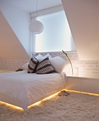 Double bed and sideboard with integrated, indirect lighting in modern attic room