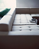 Designer couch with light upholstery and small side table